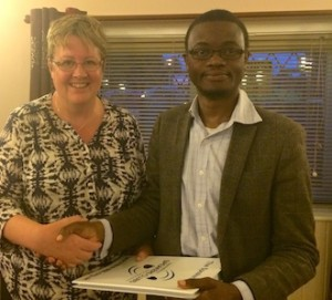 New speakers club member Apollo Kawoya receives his Speakers Guide from club President - Sue Shaw
